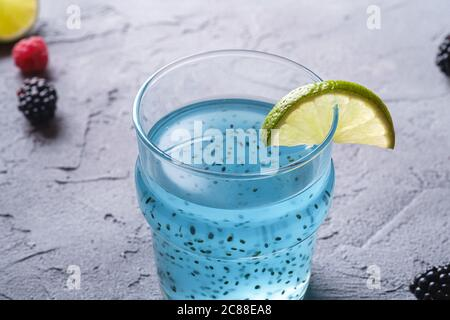 Tasty blue colored cocktail drink with basil chia seeds, citrus lime slice, raspberry and blackberry berries in glass, healthy summer beverage