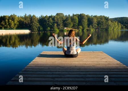 young woman on wooden pontoon or pier  practicing yoga & relaxing on holiday .