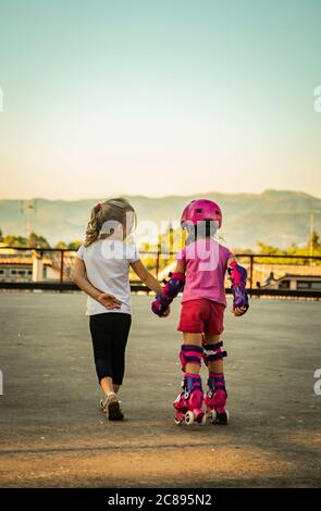 A little girl holds her best friend by the hand who is learning to skate. Concept of friendship, love, tenderness, sweetness, help, solidarity