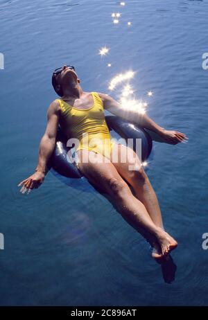 A young woman swimmer floating in an inner tube on a pond in Pennsylvania's Pocono Mountains.