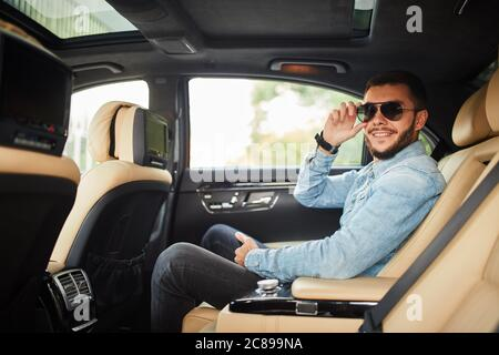 joyful young man in denim jacket sitting on the car and posing to the camera. side view photo. - Stock Photo