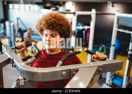 Overweight young man exercising in gym to achieve goals