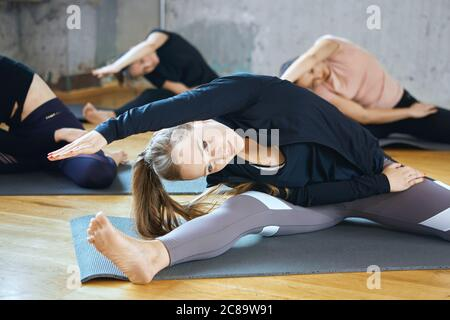 Front view of group of attractive sport girls in sportswear working out yoga in fitness hall. Selective focus of young fit women stretching on mats in gym. Loft interior. Concept of sport.