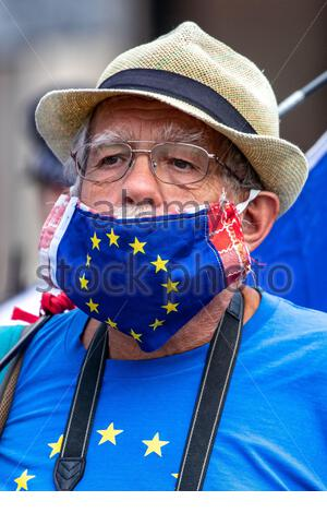 London, UK. 22nd July 2020. An anti-Brexit campaigner wearing a surgical face protective mask resembling EU's Flag holds up a banner outside Parliament in Central London on Wednesday, July 22, 2020.The British government - under the Conservative Party leadership of David Cameron, Theresa May and Boris Johnson - failed to conduct serious assessments of Russian attempts to interfere with British elections, including the 2016 Brexit referendum, according to the long-delayed 'Russia Report' released on Tuesday. (VXP Photo/ Vudi Xhymshiti) Credit: VX Pictures/Alamy Live News - Stock Photo