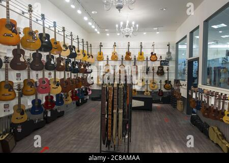 Acoustic and Electrical Music Instruments on Display in Guitar Shop Interior. Calgary, Alberta Market Mall Shopping Centre Stock Photo