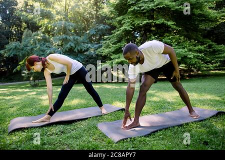 Horizontal shot of young fit multiethnic couple, African man and Caucasian woman, doing sport and yoga exercises outdoors. Stretching in park during - Stock Photo