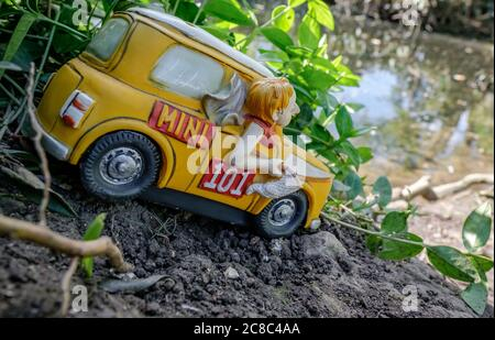 Miniature, ceramic styled small model of a hatchback car shown in various positions in a large, residential garden. - Stock Photo
