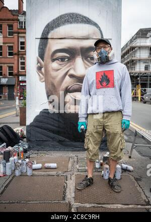 Portrait of Street artist, Akse_19, standing in front of his murals - Stock Photo