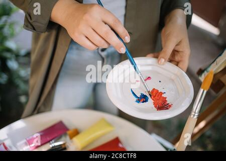 Female artist hands mixing paints in plate - Stock Photo