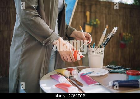 Close-up view of woman's hand squeezing paint tube