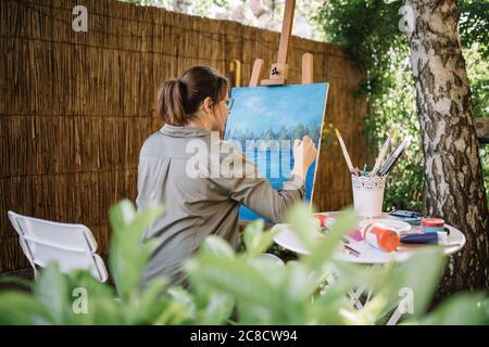 Back of female artist painting with paintbrush - Stock Photo