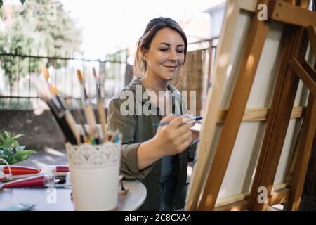 Young female artist enjoying painting in backyard - Stock Photo