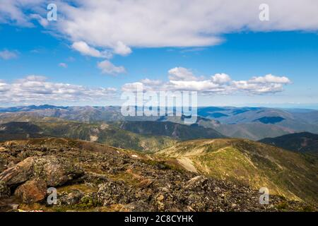 Magnificent view of the mountains from Chersky Peak. Mountain peaks of Khamar-Daban in summer against the background of blue sky and clouds.