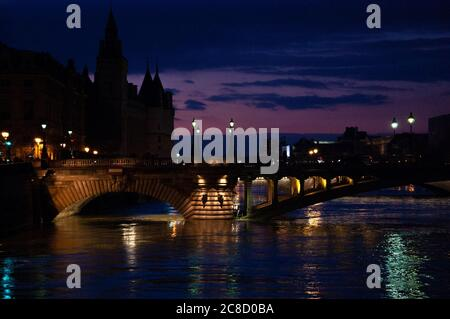 Blue hour in Paris. View of Pont au Change bridge and Conciergerie building. Colorful reflection of evening city lights in Seine river water. - Stock Photo