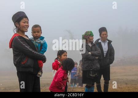 Sapa, Vietnam - January 16th 2014: Hmong people and the children on a cold, misty morning in Sapa, Vietnam - Stock Photo