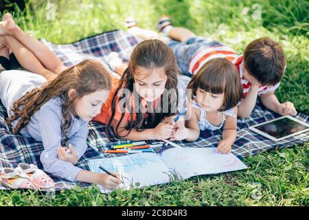 group of Childs painting at easel in park