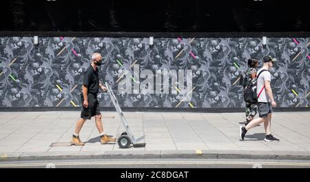 London, UK. 23 July 2020. London remains quieter than pre-Coronavirus times with a lack of tourists and many commuters remaining on furlough or home-working. Many people on London's streets (photo: Oxford Street) now wear masks as the city gradually relaxes lockdown measures. Credit: Malcolm Park/Alamy Live News. - Stock Photo