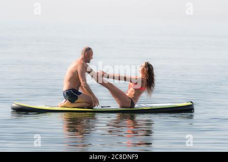 Mature couple practicing yoga together on paddleboard over sea - Stock Photo