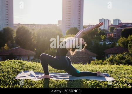 Young woman practicing yoga in warrior position at city park during sunny day