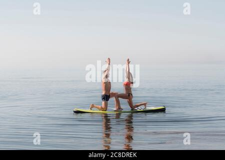 Couple practicing yoga together on paddleboard over sea - Stock Photo