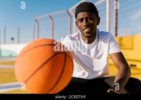 Smiling young man holding basketball while sitting in court during sunny day
