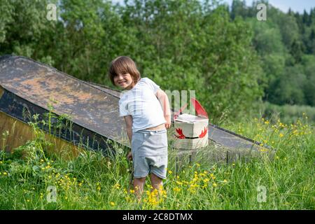 Smiling boy with mask on abandoned boat standing amidst plants in forest - Stock Photo