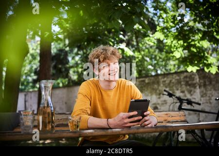 Portrait of young man sitting at beer table in garden with digital tablet