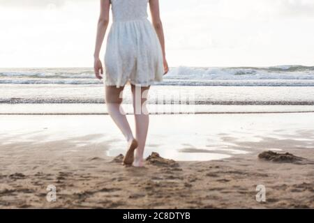 Young woman wearing white dress walking barefoot on sand at beach against clear sky - Stock Photo