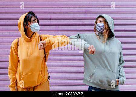 Young woman wearing masks greeting with elbow - Stock Photo