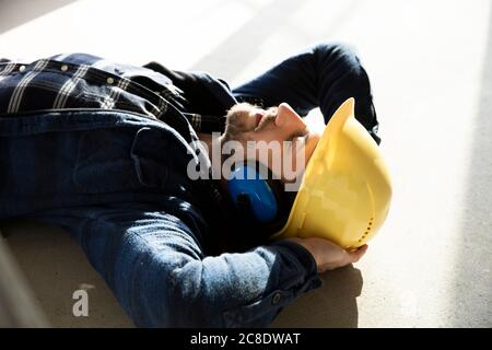 Close-up of construction worker with hands behind head sleeping on floor in renovating house