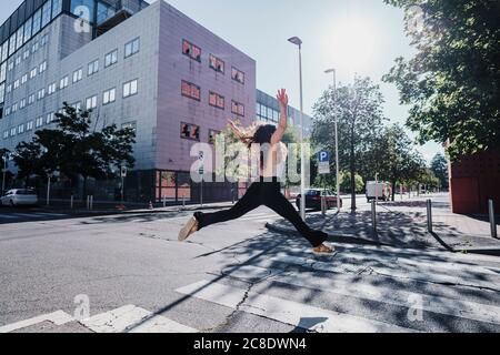 Excited young woman jumping on city street during sunny day - Stock Photo