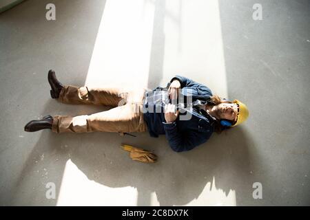 Construction worker sleeping on floor in renovating house