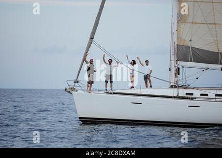 Happy friends waving while standing on sailboat in sea