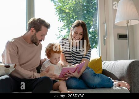 Smiling woman reading picture book while sitting by son and man on sofa in living room at home - Stock Photo