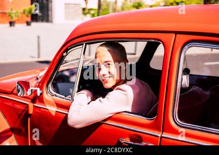 Portrait of happy teenage boy sitting in vintage car looking out of window - Stock Photo