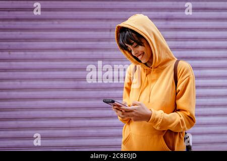 Portrait of young woman with yellow hoodie checking smartphone in front of purple background