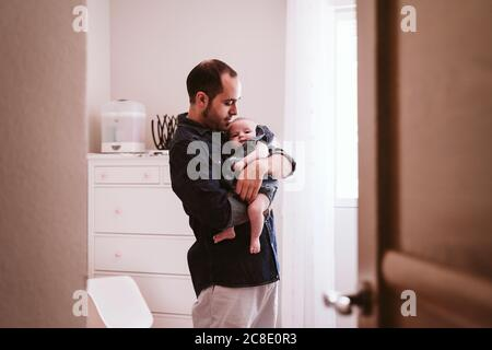 Father carrying cute baby girl in living room at home