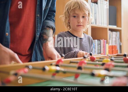 Father and son playing foosball at home - Stock Photo