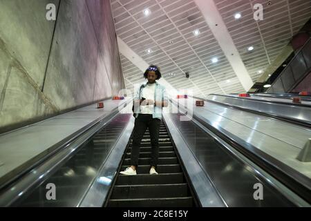 Young trendy man using smart phone on escalator at subway station - Stock Photo