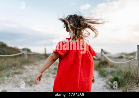 Playful girl walking at beach against cloudy sky - Stock Photo
