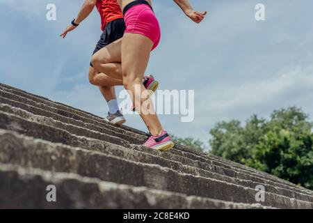 Close up and low below angle view photo of athletes legs running up concrete stairs