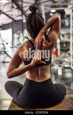 Young woman with braided hair stretching hands while sitting on table in gym