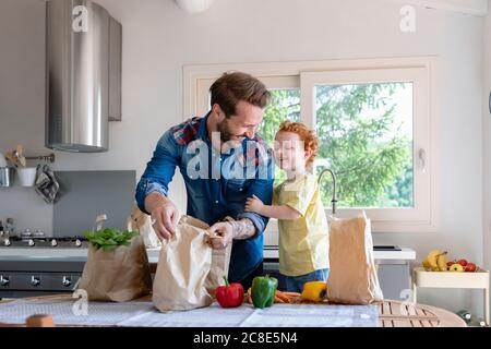 Cheerful father and son with groceries standing at dining table in kitchen