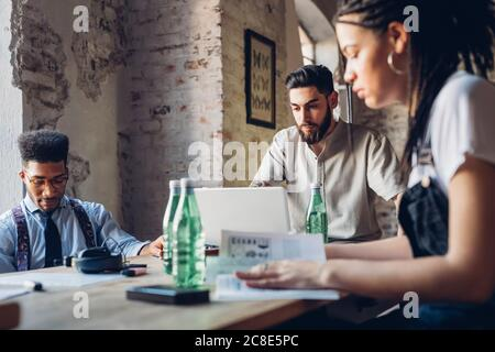 Creative business people working at table in loft office Stock Photo