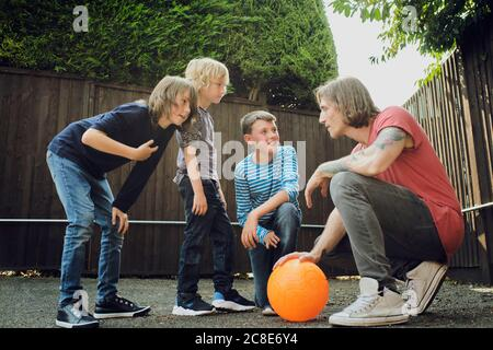 Man and boys discussing strategy over basketball at yard - Stock Photo