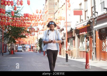 Young man walking on street looking at smartphone, Chinatown, London, UK - Stock Photo