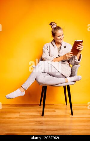 Happy woman using digital tablet while sitting on chair against yellow background - Stock Photo