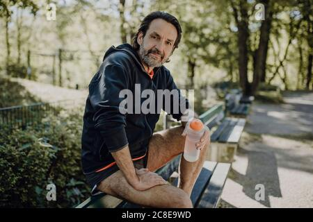 Confident mature man holding water bottle while sitting on bench in park