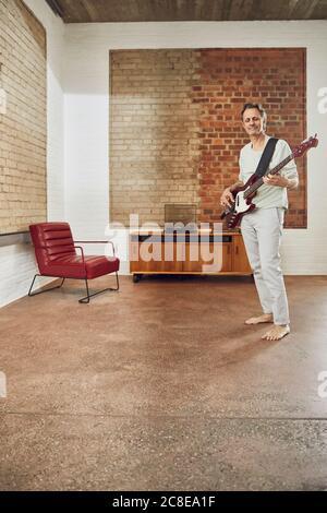 Senior man playing bass guitar in a loft flat