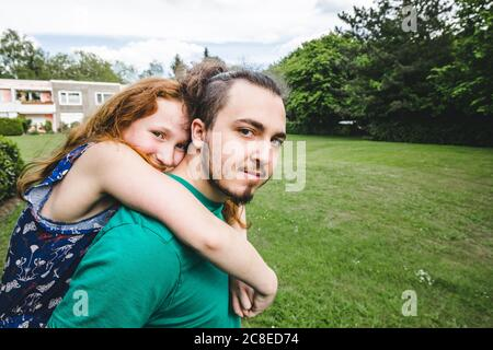 Smiling girl embracing young brother while standing in yard - Stock Photo